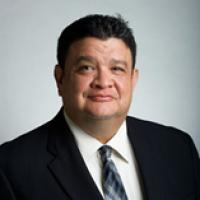 Latino man, short dark hair, wearing white shirt, striped tie, and black jacket smiling at the camera