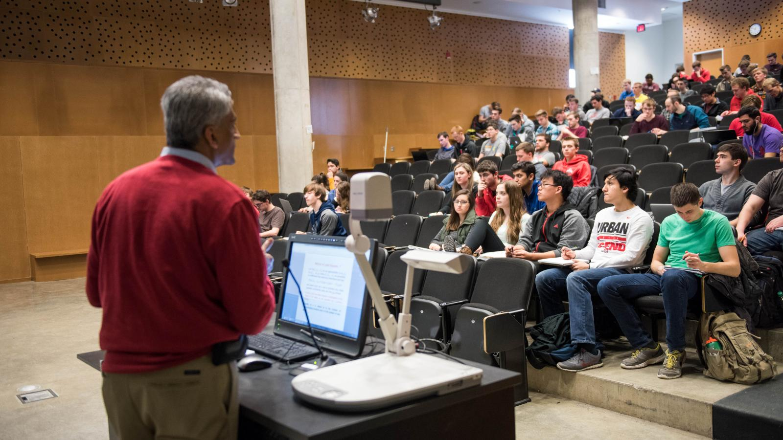 Male teacher standing in front of lecture hall full of students